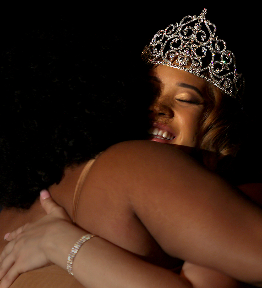 Cheryl-Anne Johnson, the winner of the Black and Gold Scholarship Competition, hugs Emonie Jordan, who helped train the contestants and co-cordinated the pageant, after she was crowned Friday night in the Martin Luther King Jr. University Union Grand Ballroom.