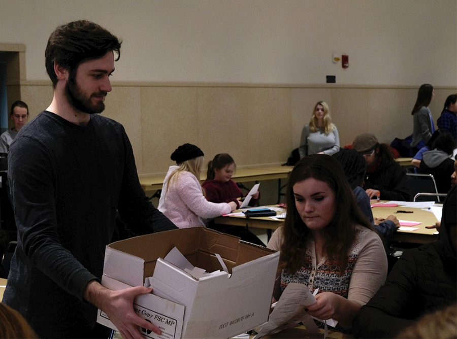 Will Taylor, a student worker at the office of Civic Engagement and Volunteerism and a junior human resources major, collects the scrapes leftover from the recipe books volunteers were making at the Martin Luther King Jr. Day of Service Monday afternoon at the University Ballroom.