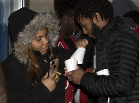 Kaleb Williams (right), a senior kinesiology and sports studies major, lights another student's candle during the Martin Luther King Jr. Vigil and March Monday night at Thomas Hall.