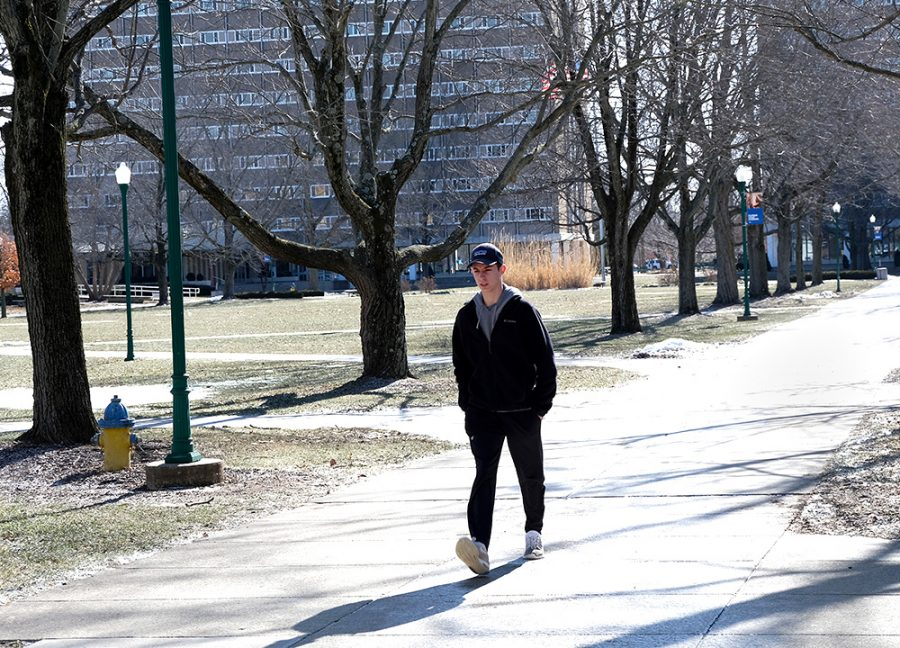 Andrew Agoranos, a freshman criminology major, walks outside of Coleman Hall in the cold weather Monday afternoon.