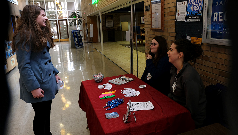 Andrea Carey, a hiring associate, and Rachael Croy, a chief scribe at ScribeAmerica, talk to a student at a table they set up in the Martin Luther King Jr. University Union Thursday afternoon. They were offering employment opportunities as a medical scribe. According to their informational handout, a medical scribe is essentially a personal assistant for a physician; they document and gather information on patient visits.