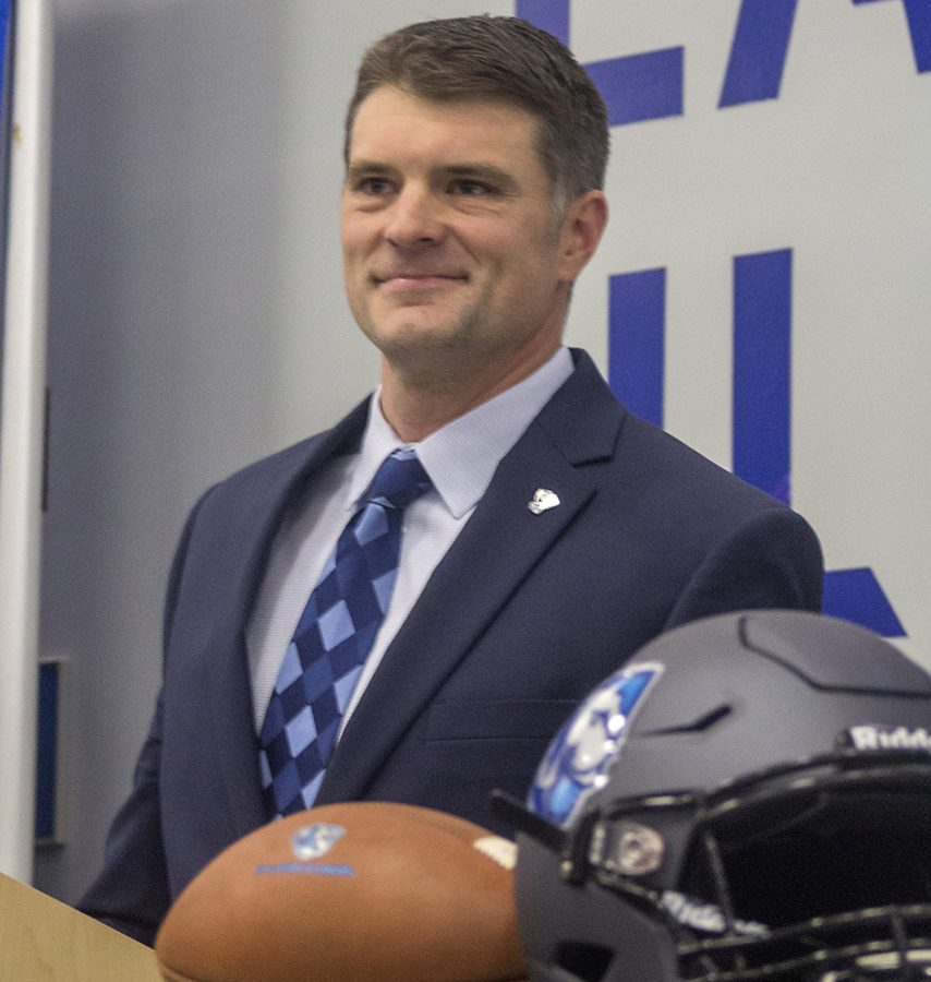 Adam+Cushing%2C+the+new+head+coach+of+the+Eastern+football+team%2C+accepts+applause+after+giving+a+press+conference+in+December+2018.+Cushing+hired+John+Kuceyeski+as+his+offensvie+coordinator.