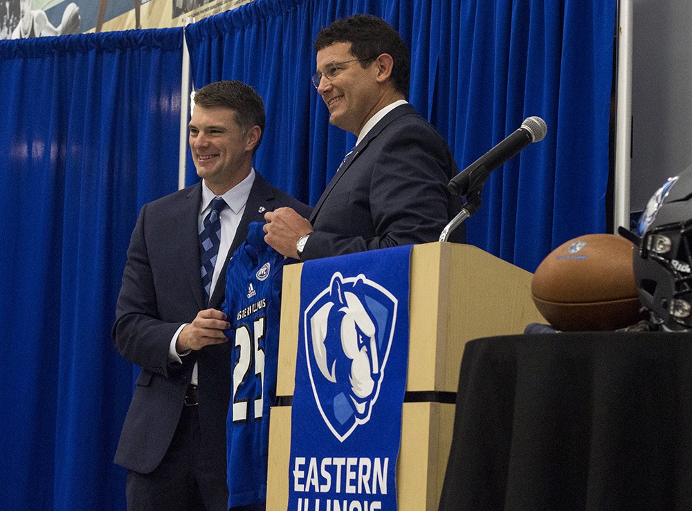 Analicia Haynes | The Daily Eastern News Adam Cushing (left) accepts an Eastern football jersey from Athletic Director Tom Michael during a press conference in December 2018. Cushing added Chris Bowers and John Kuceyeski to be his defensive and offensive coordinators.