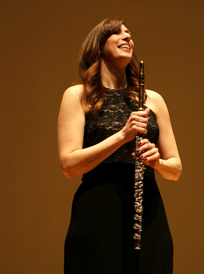 Erin Helgeson Torres, flutist for Tower Duo, goes for a bow after performing one of their songs Wednesday night in the Doudna Fine Arts Center.