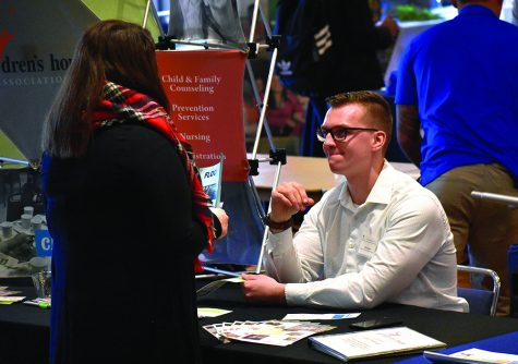 Tim Reiner, a HR Generalist at Children's Home Association of Illinois, talks with student during Job & Internship Fair at Grand Ballroom of MLK University Union on Wednesday afternoon.