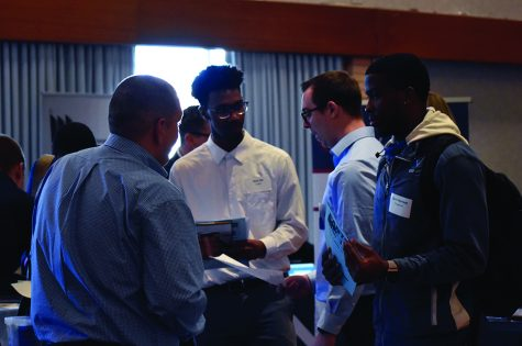 Devin Morrison (right), a management freshman, is hearing recruitment information from The Sherwin-Williams Company during Job & Internship Fair at Grand Ballroom of MLK University Union on Wednesday afternoon.