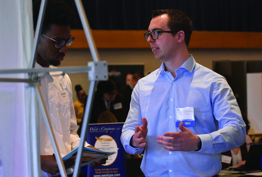 Spencer Briggerman (right), a assistant manager at The Sherwin-Williams Company and a Eastern alumni, is talking to a English student Dom Hill (left) during Job & Internship Fair at Grand Ballroom of MLK University Union on Wednesday afternoon.