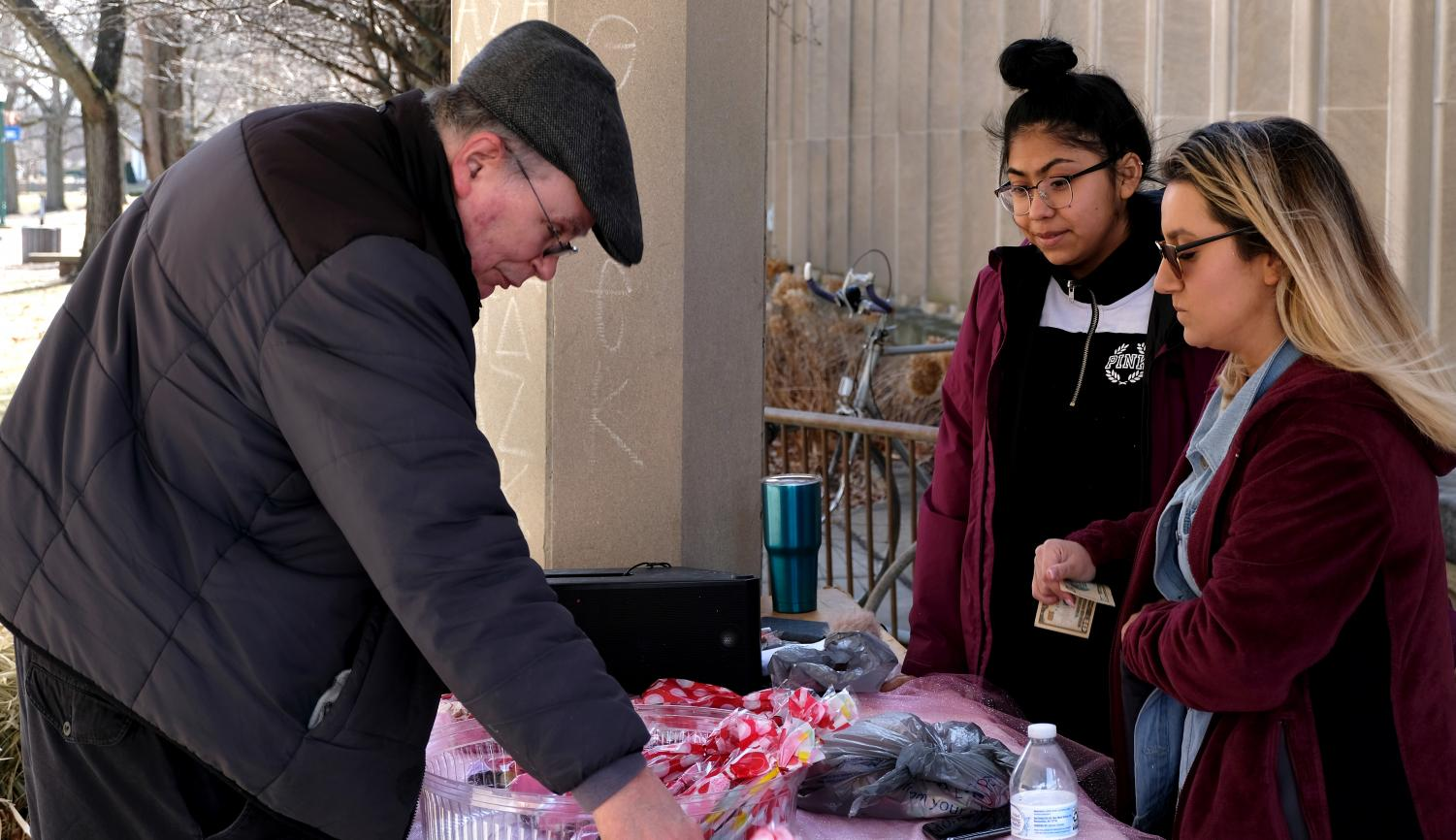 Esperanza members Yrely Robledo, an accounting major, and Gina Canchola a business management major, sell a man chocolate covered deserts Thursday afternoon outside of Coleman Hall.