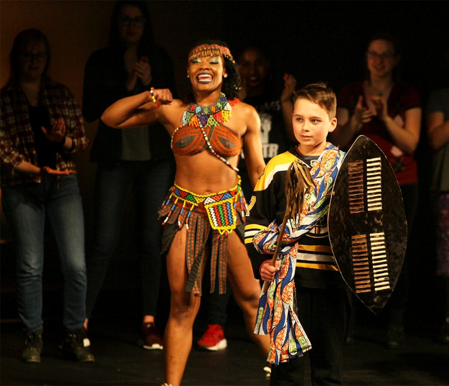A participant from the audience joins the Ndlamu dance during the Step Afrika! concert Saturday night in the Doudna Fine Arts Center.