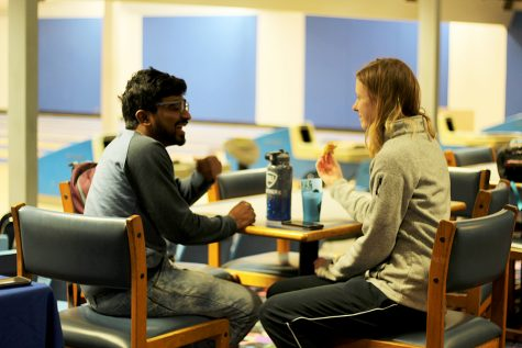 """Subha Chandrasekhar, a graduate in technology, and Taylor Powers, a senior in recreation administration, attend the Karaoke Bowling event held by the Univeristy Board in the bowling alley of the Martin Luther King Jr. University Union. The two enjoy pizza provided at the event on Tuesday evening. """"I saw it on Facebook and I like bowling, so I thought it would be fun,"""" Powers said about her interest in the event."""