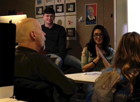 Vanessa Lopez (center), a senior graphic design major, pitches her design to Joe Judd (left), owner of Bob's Bookstore, Wednesday afternoon in the Doudna Fine Arts Center.