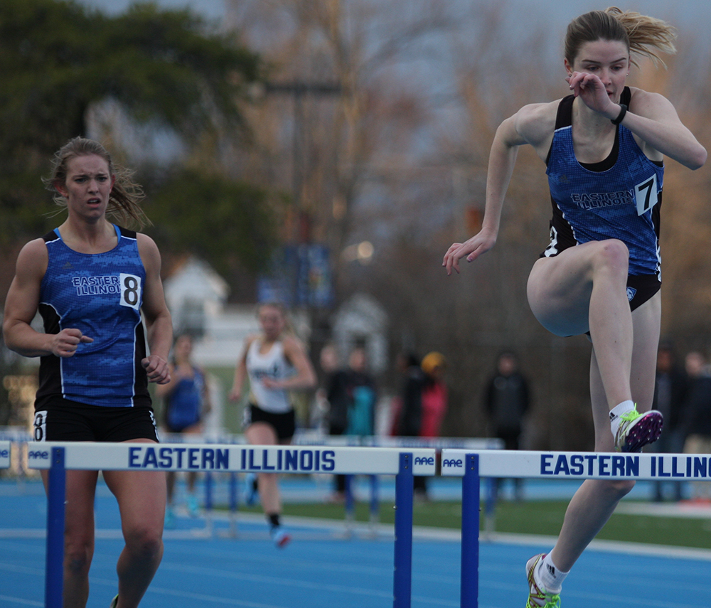 Morgan Atchison (left) runs during the hurdles event while Louisa Rieger (right) clears a hurdle during the EIU Big Blue Classic in March 2018 at O'Brien Field.