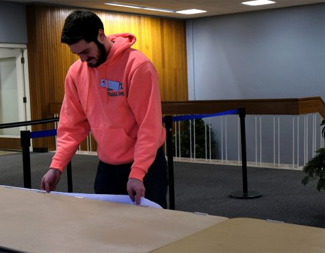 Student Worker Will Taylor, a junior human resources major, sets up a table for an upcoming event Wednesday afternoon outside of the Grand Ballroom in the Martin Luther King Jr. University Union.