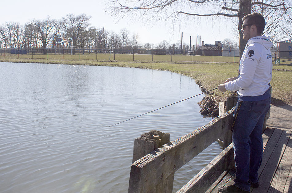 Theo Laleian, a junior computer information technologies major, fishing on the dock at the Campus Pond.