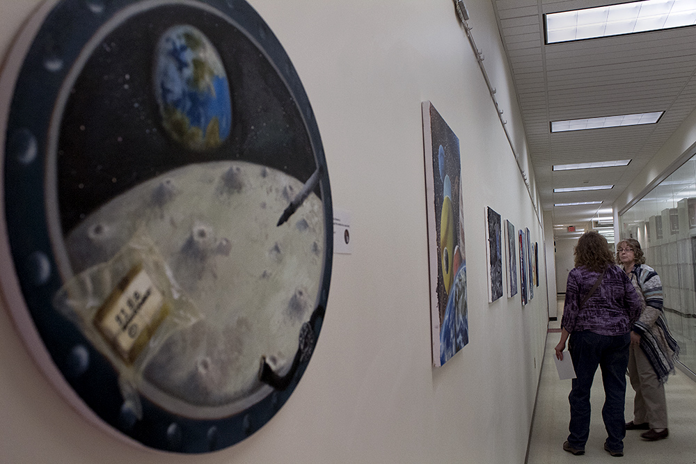 """Beth Heldebrandt, public relations director at Booth Library, and Cindy Bettinger, an art major, get ready to film a video for Booth Library's website. Bettinger is the artist of """"Hazy Moon,"""" and says she dreams of the universe with her paintbrush."""