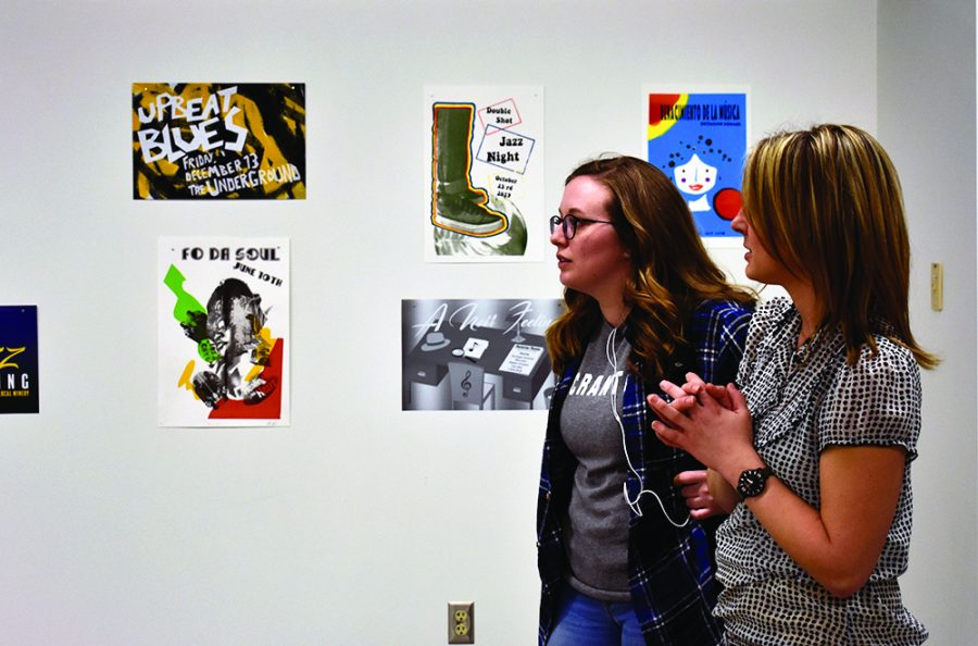 Samantha Osborne (right), a professor of graphic design, talks about artwork exhibited at the Frequency Response Show with Stevie Roberson (left), a graduate art student, in the Gallery 1910 of the Doudna Fine Arts Center on Wednesday afternoon. The Frequency Response Show exhibits three disciplines's art works, includes painting, printmaking and graphic design. Students create their poster, print or painting based on one of the various music tracks that they were provided.