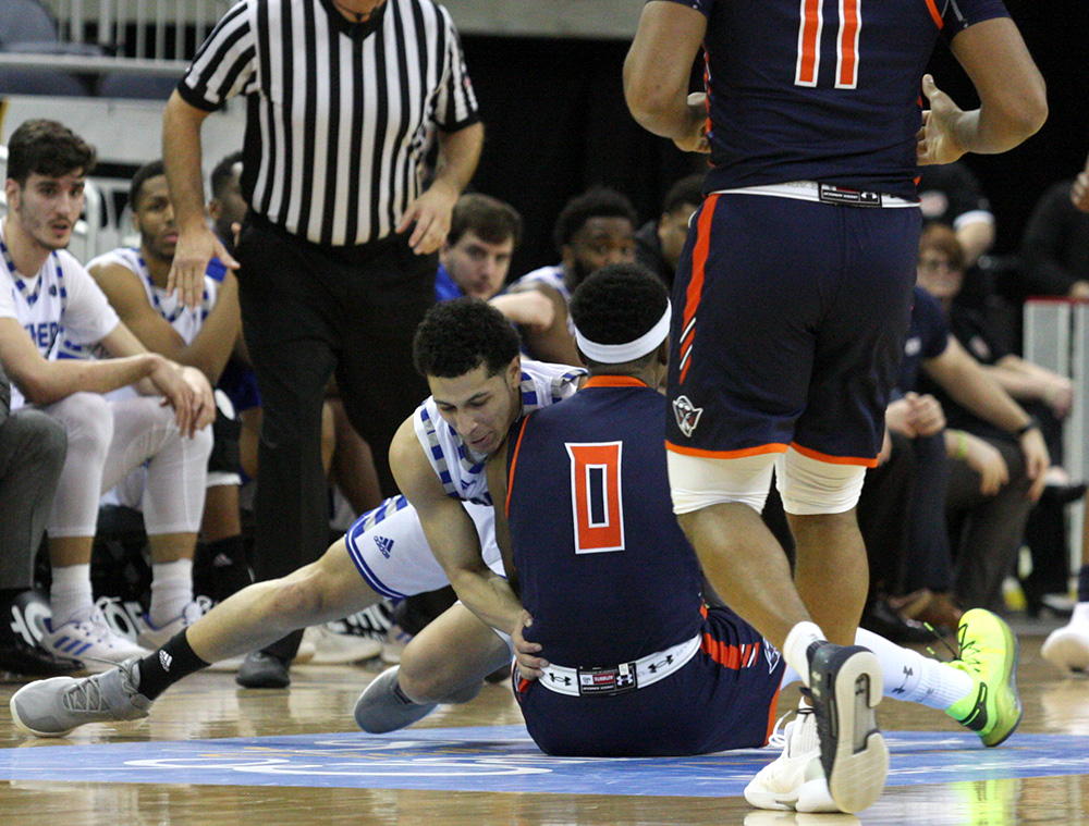 Eastern Shareef Smith grapples with Tennessee-Martin's Preston Parks for a loose ball on one of the on-court emblems Eastern head coach Jay Spoonhour questioned the quality of. Five total players slipped on these logos during the game.