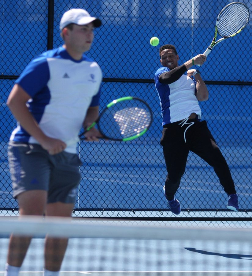 Jared Woodson jumps and returns a hit during a doubles match with partner Gage Kingsmith in the men's tennis team's 7-0 loss to Belmont at the Darling Courts in March of 2018.