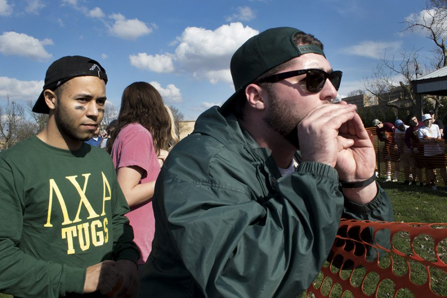 Members of the Lambda Chi Alpha cheer on Sigma Kappa during their tug of war match at the campus pond on Monday afternoon. As Sigma Kappa slowly started to lose ground, the two began to shout encouragement to the sorority.