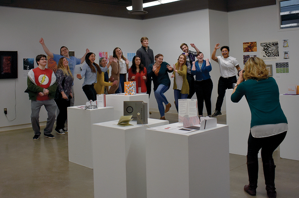 Senior graphic design students get their group picture taken at their 2019 BFA Graphic Design Show in Gallery 1910 of the Doudna Fine Arts Center on Wednesday afternoon.