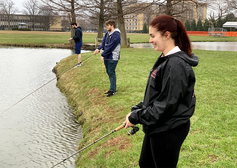 Elizabeth Walters, a junior psychology major, fishes during a light drizzle Thursday afternoon at the Campus Pond near Lantz Arena.