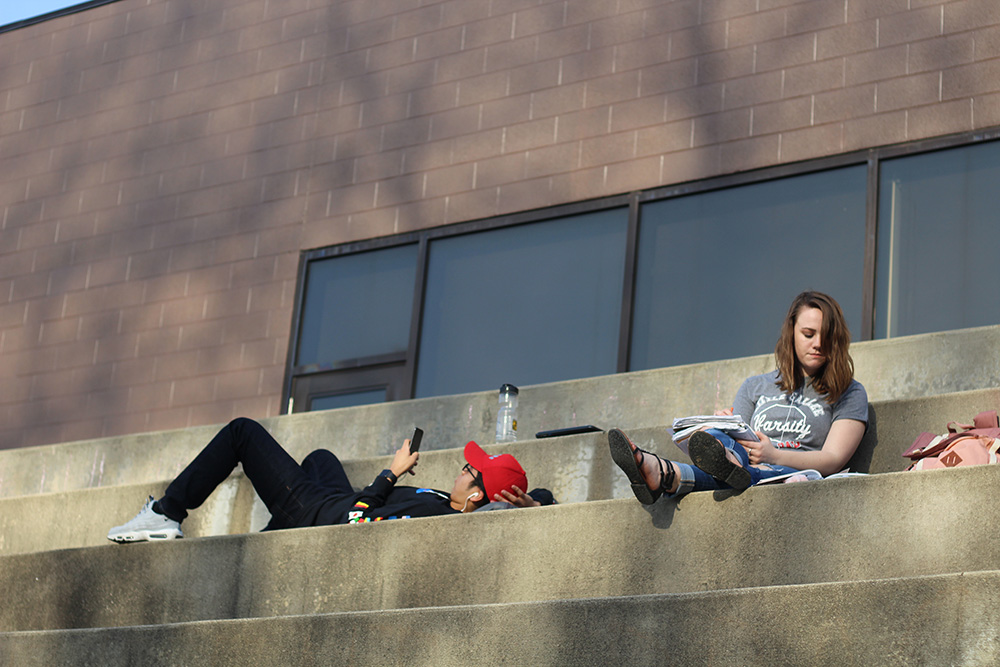 Vincent Rodriguez (left), a freshman engineering technology major, and Kat Stephens (right), an elementary education major, relax and enjoy the weather on the steps of the Doudna Fine Arts Center Sunday afternoon.