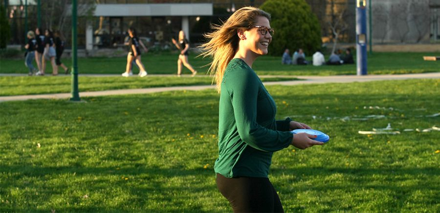 Kaitlyn Ebert, a senior public relations and political science major, smiles while playing catch Wednesday afternoon in the South Quad.