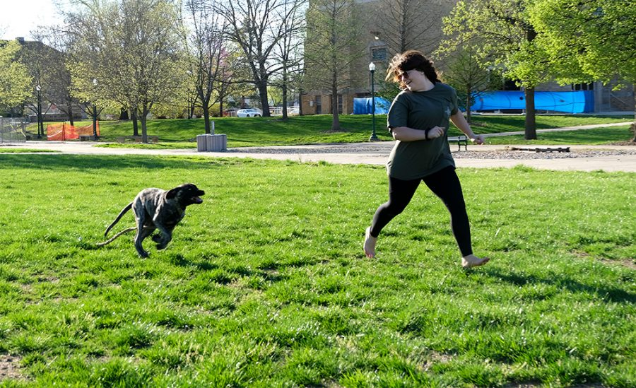 Katie Conlin, a sophomore special education major, runs with a dog named Lucky Monday afternoon at Pets with the Prez in the Library Quad.