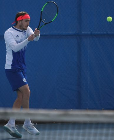 Daniel Hernandez returns a hit with a backhand hit of his own in his singles match during Eastern's 6-1 loss to Jacksonville State March 22 at the Darling Courts.