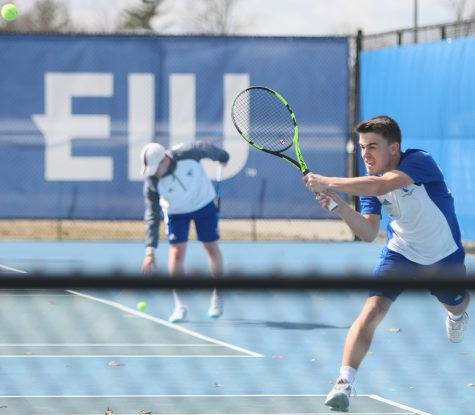 Gertjan De Wilder hits a backhanded shot in his doubles match during the Eastern men's tennis team's 6-1 loss to Jacksonville State March 22 at the Darling Courts.