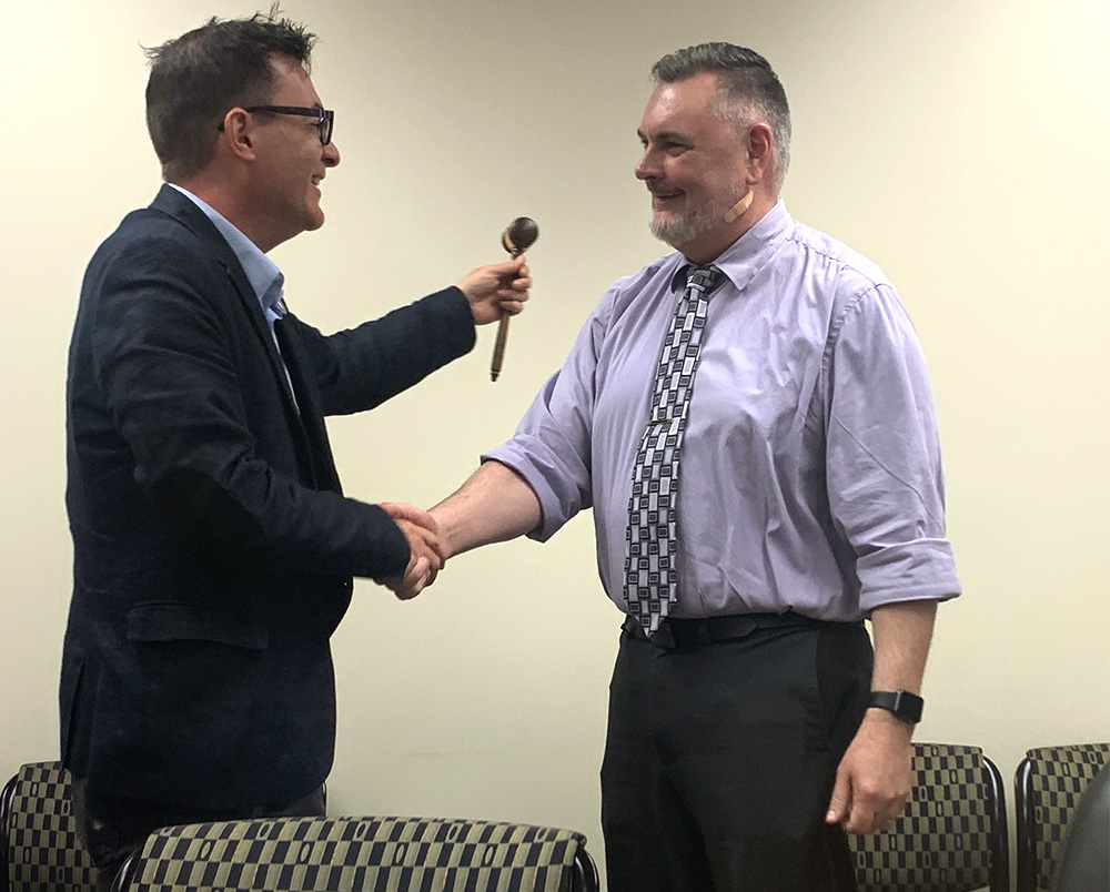 Faculty Senate member C.C. Wharram (left) accepts the gavel from Todd Bruns, the 2019 Faculty Senate chair, on May 2 during the Senate meeting at Booth Library. Wharram will be the next chair for the Senate starting in the fall.