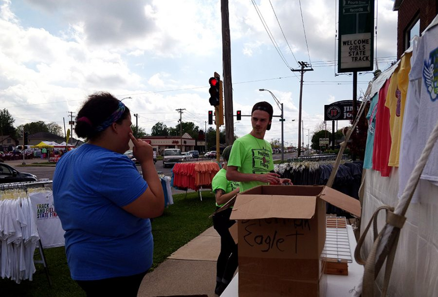 Brady Stone (right), an associate for Positively 4th Street, and Callie Luttman (left), another associate who graduated in May with a bachelor's in public relations, set up tables in front of the store for the IHSA Girls Track and Field semifinals and finals Wednesday afternoon. Stone said that he loves seeing all the people from all over the state of Illinois come to visit Charleston.