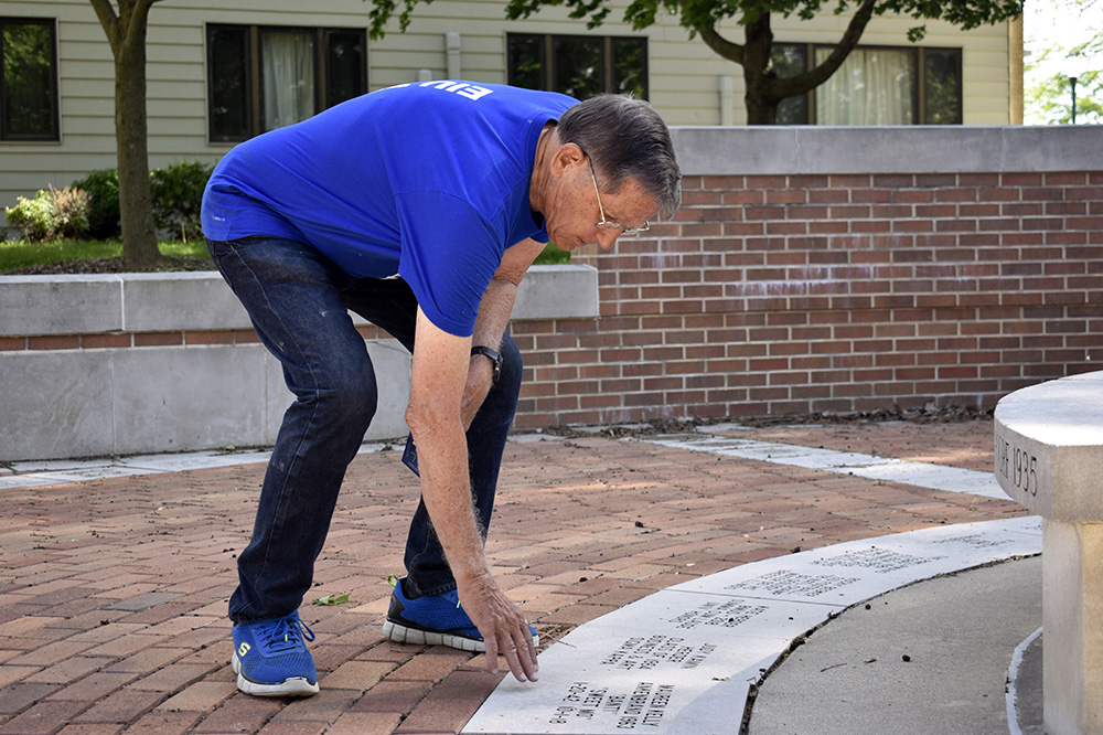 Larry Ankenbrand, a retired KSS professor, strokes the name slate belonging to his wife, Maureen, Sunday afternoon at the Commemorative Courtyard.