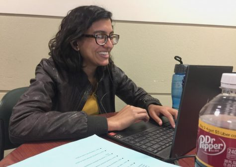 Humaira Ahmed, a counseling graduate student, works at her laptop for one of two classes she is taking over the summer at the Buzzard Hall Atrium.