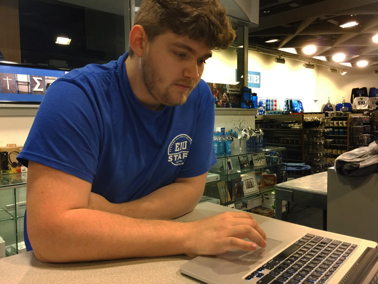 Evan Boggs, senior graphic design major and head of graphic design at Eastern's Bookstore, scrolls through advertisements he has created for the store Wednesday afternoon.
