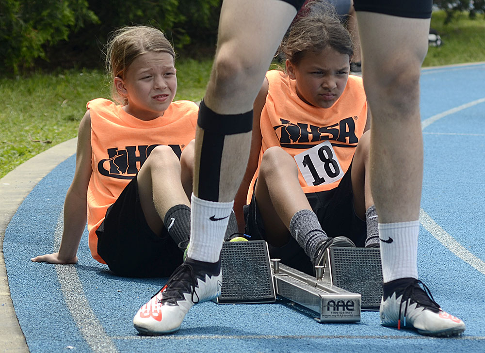Two girls volunteering for the Illinois High School Association, put their feet on the starting block for a high school competitor during the 4x400-meter relay Class 1A preliminary Thursday at O'Brien Field.