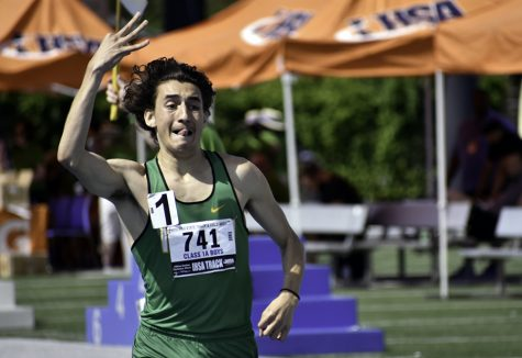 Christopher Collet, a senior from Seneca High School, holds up three fingers, alluding to the triple crown, as he crosses the finish line in first place with a time of 4:24.71 during the final 1600-meter run in Class 1A on May 25. Collet was competing in the Illinois High School Association Boys Track and Field state semifinals and finals, which took place at O'Brien Field May 23 through May 25. He also earned first place in the prelim 1600-meter run with a time of 4:25.16 and first place in the final 3200-meter run with a time of 9:36.99.