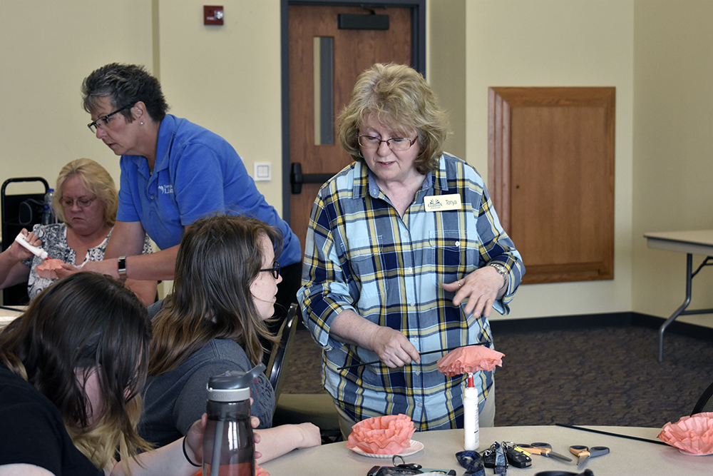 Tonya Morton, an employee of the Charleston Carnegie Public Library, teaches people how to use coffee filters to craft into flowers at the Rotary Room B Tuesday evening.