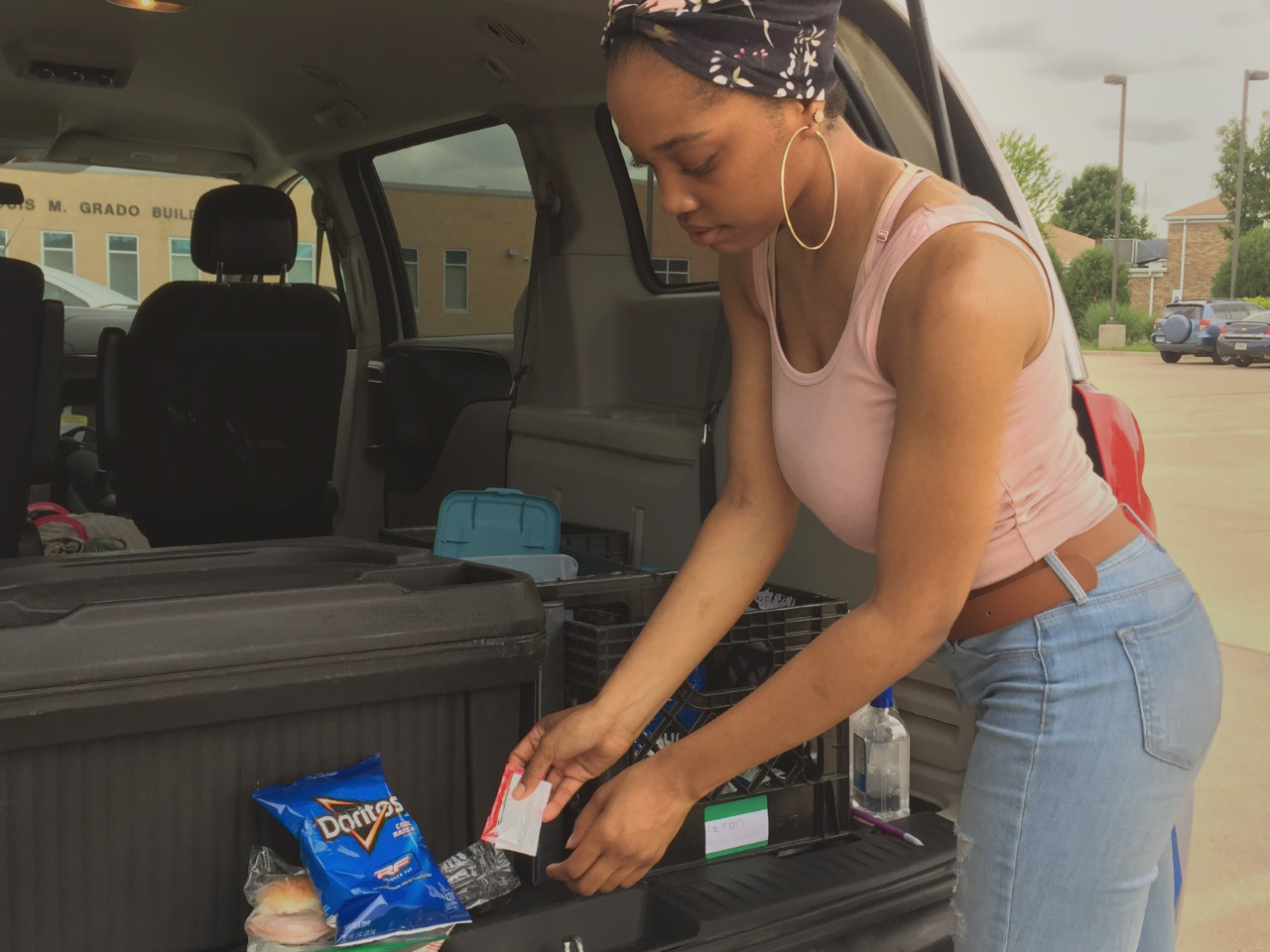 Monica Maybell, a dietetics senior and student worker, organizes a meal as part of the Office of Civic Engagement and Volunteerism and Salvation Army's summer free meals program for youth on Wednesday at Textbook Rental.