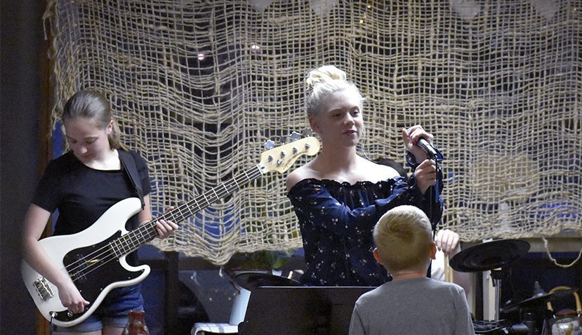 Nora Gannaway, 13, puts the microphone back on its stand after singing a song at SweeTea'z Thursday evening. Gannaway is a singer from the local band Janoma, which is made up of young teens.