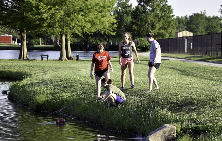 Karyn Baldwin (left), Courtney Prais (right), Mallory Johnson (middle) and Nora Richardson play with a football next to the Campus Pond Tuesday afternoon. Richardson is using a branch to retrieve the football back after dropping it into the water.