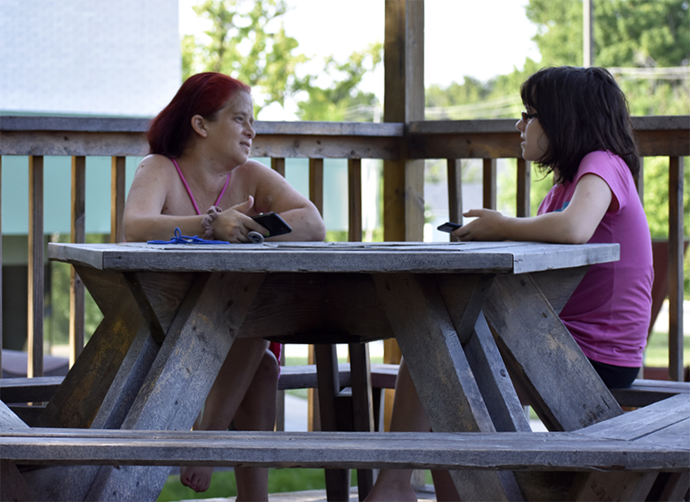 Heather Davis, 42, and Hannah Hudson, 14, relax in the pavilion outside the Tarble Arts Center Tuesday afternoon.