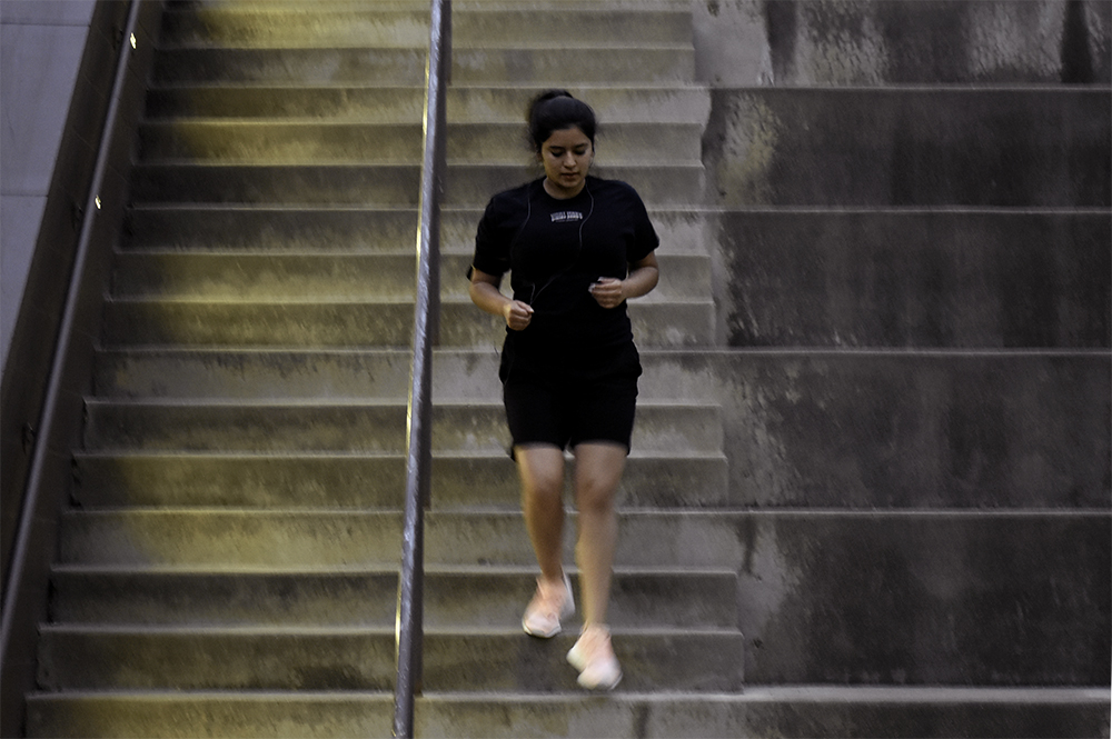 Jessica Valenzuela, a senior Elementry Education student from the University of Illinois at Urbana-Champaign, climbs stairs back and forth on Wednesday evening at the Mellin Steps outside the Doudna Fine Arts Center.
