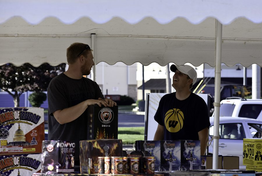 Tristan Warner (right) from Warner Enterprises talks with a customer at a set of merchant tables at an empty space next to Arby's Monday. He said Warner Enterprises provides premier consumer fireworks across the state.