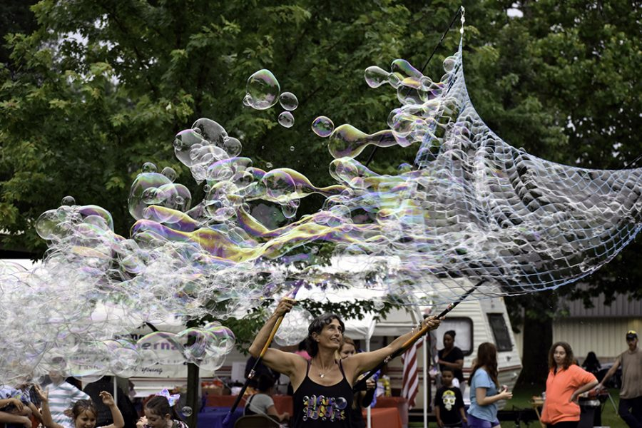 Rae Spooner uses a large net to blow multiple large bubbles Wednesday at Morton Park. She said the rain was not good for the bubbles; however, the humidity from the rain is actually helpful to the bubbles.