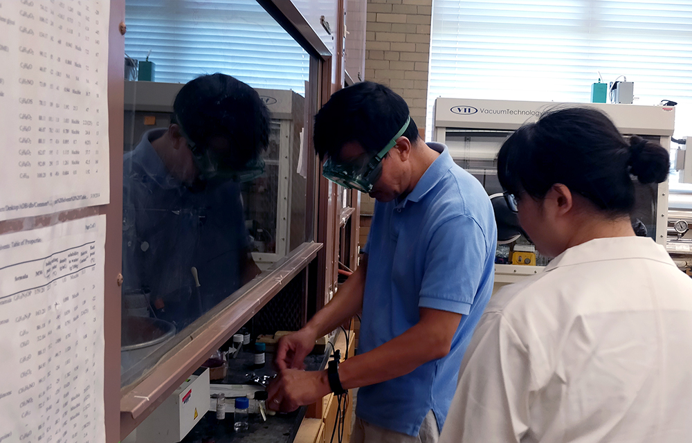Hongshan He (left), a chemistry professor, instructs Beibei Liu, a research assistant, on how to use a spin coater in the Physical Sciences Building Monday afternoon.