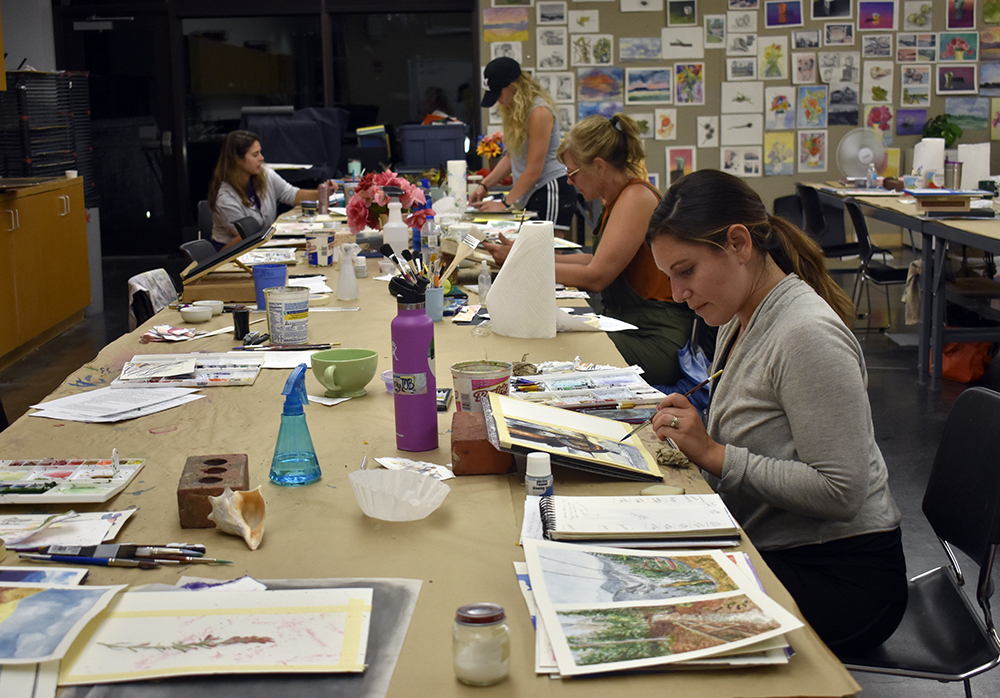 Graduate art education students paint watercolor in room 2690 at the Doudna Fine Arts Center Wednesday night.