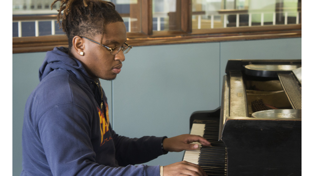 Ozzie Gardner, a freshman whose major is undecided, plays a melody on the piano in the lobby of Lawson Hall on Thursday afternoon.