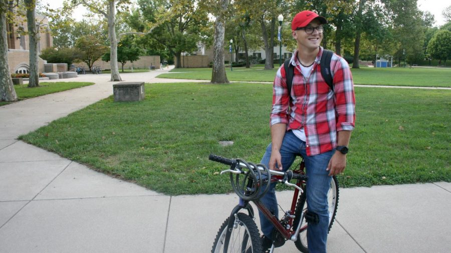 Matthew+Riley%2C+a+sophomore+double+majoring+in+psychology+and+criminology%2C+stops+on+his+bike+to+say+%27hi%27+to+a+friend+Monday+at+the+Library+Quad.+Riley+said+he+rides+his+bike+everywhere+on+campus+every+day.+