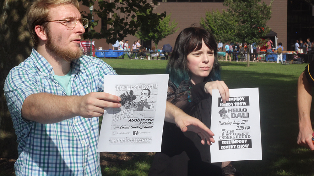 McClain Homan, a sophmore geography major, and Hannah Donegan, who is studying TV and video production, wave flyers for the Hello Dali shows and auditions at the Student Involvement Fair in the libray quad on Tuesday afternoon. Auditions are September 5 and 6 at 8:00 p.m in Coleman auditorium, room 1255.